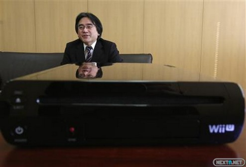 Nintendo Co's President Satoru Iwata speaks next to company's Wii U game console during an interview with Reuters at the company headquarters in Kyoto, western Japan